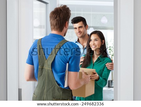 Young couple receiving package from delivery-man at home. - stock photo