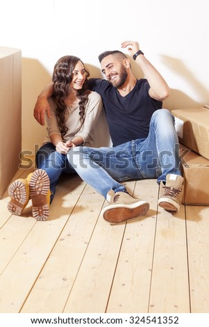 young couple relaxing after moving between the boxes