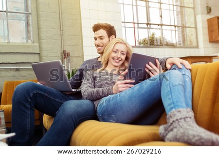 Young couple relaxing at home catching up on social media as they relax close together on a sofa in the living room working on a tablet and laptop computer - stock photo