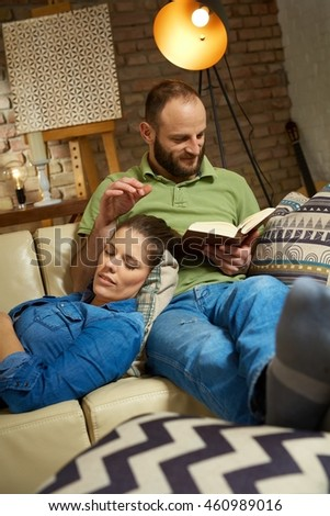 Young couple relaxing at home on sofa, man reading woman sleeping.