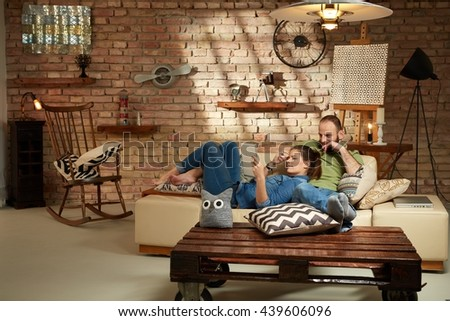 Young couple relaxing at home, using tablet. - stock photo