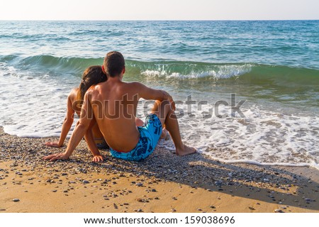 Young couple relaxing at the beach in late afternoon