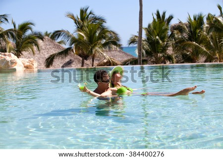 Young couple relaxing in resort swimming pool and drinking cocktails. Couple Enjoying Romantic Holidays. - stock photo