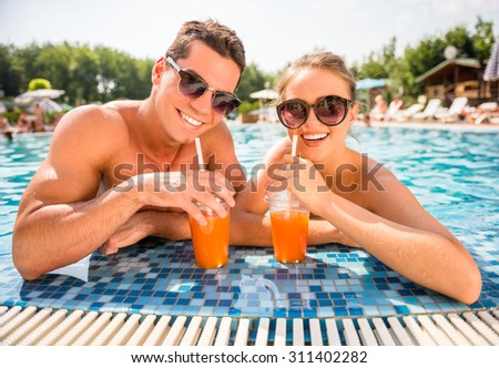 Young couple relaxing in resort swimming pool, drinking cocktails. - stock photo