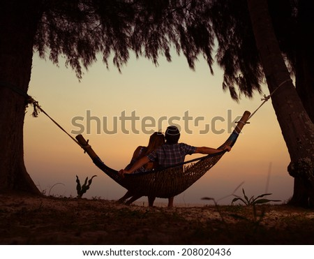 Young couple relaxing in the hammock at sunset - stock photo