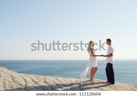 Young couple relaxing near the sea while standing on a rock