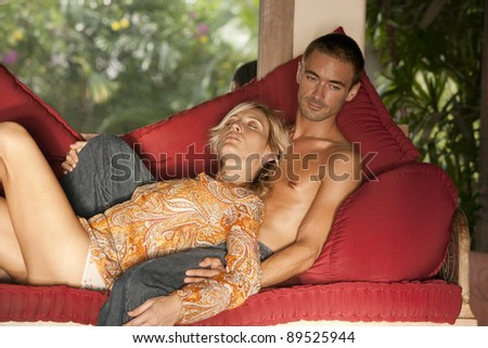 Young couple relaxing on a red sofa while on vacation. - stock photo
