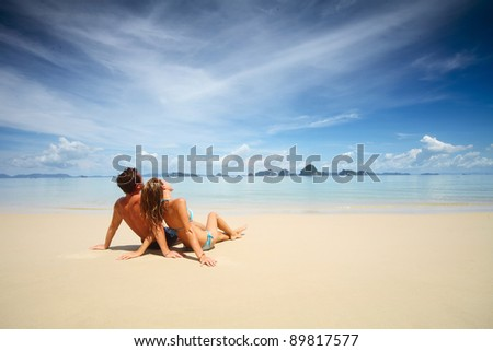 Young couple relaxing on a warm tropical sand - stock photo