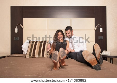 Young couple relaxing on bed while surfing the web with tablet in luxury hotel room.  - stock photo