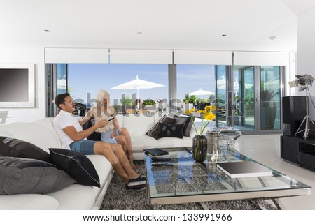 Young couple relaxing on couch in luxury living room - stock photo