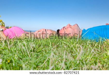Young couple relaxing on grass in park against blue sky - stock photo