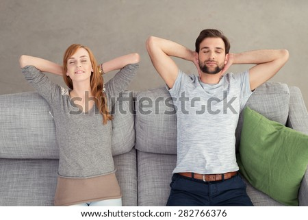 Young Couple Relaxing on Gray Couch with Hands On the Back of their Heads and Eyes Closed. Captured in High Angle View