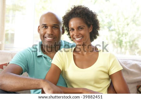 Young Couple Relaxing On Sofa At Home