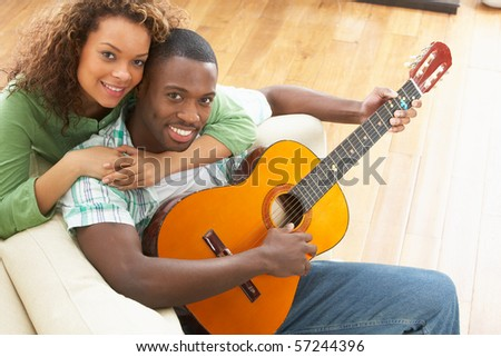 Young Couple Relaxing Sitting On Sofa Playing Acoustic Guitar - stock photo