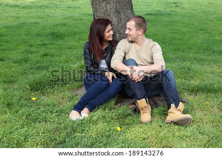 young couple relaxing under a tree - stock photo