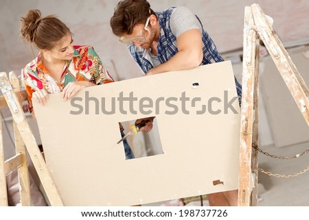 Young couple renovating home, DIY, rasping wooden panel.