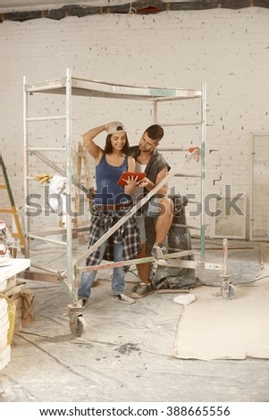 Young couple renovating home, using tablet computer. - stock photo
