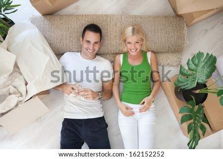 Young couple resting on floor their new home - stock photo
