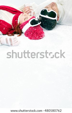 Young couple resting on snow and enjoying each other company