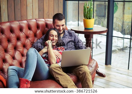 young couple resting on sofa and surfing on internet with laptop at home  - stock photo