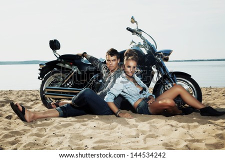 Young couple riders sitting together on sand beach by motorbike - travel concept - stock photo