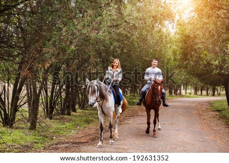 Young couple riding a brown horse at countryside at summer  - stock photo