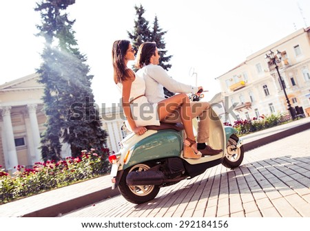 Young couple riding a scooter in old european town - stock photo