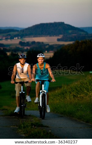 young couple riding bikes in the country - stock photo
