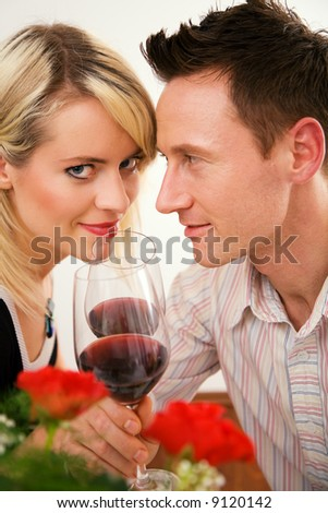 Young couple romantic dinner: clinking glasses with red wine - stock photo
