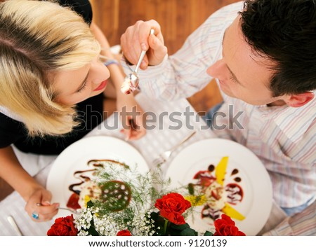 Young couple romantic dinner: he is feeding her with desert (yoghurt mousse); focus on faces - stock photo