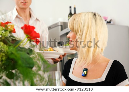 Young couple romantic dinner: he is serving her pasta; focus on the girl - stock photo