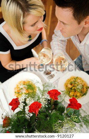 Young couple romantic dinner: letting the white wine glasses clink; focus on the eyes of the people - stock photo