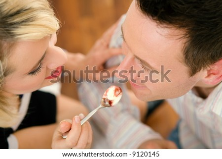 Young couple romantic dinner: she is feeding him with desert (yoghurt mousse); focus on faces