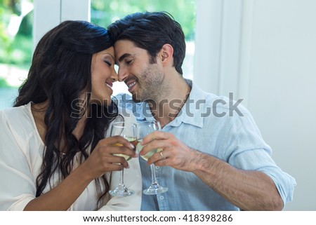 Young couple rubbing their nose while toasting wine at home - stock photo