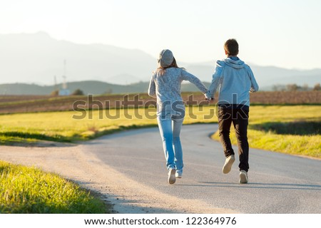 Young couple running along country road. - stock photo