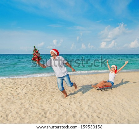 Young couple running at sea beach in red santa hats with color sled and decorated christmas tree - holiday concept - stock photo