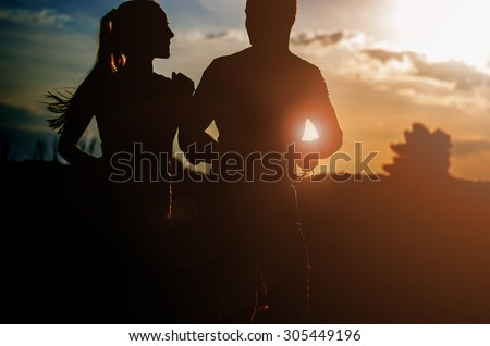 Young couple running at sunset outdoors. Solar flare illuminates a couple back.
