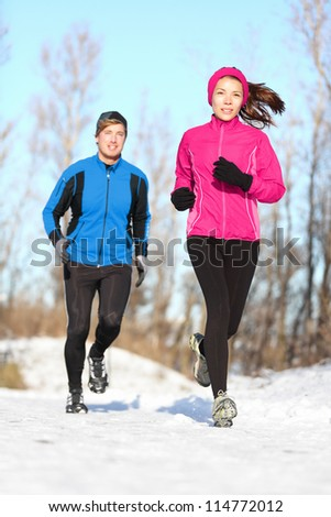 Young couple running dressed warmly in fleeces and gloves jogging in sunshine across winter snow in the countryside - stock photo