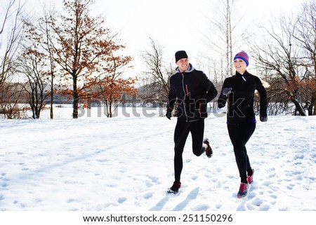 Young couple running during winter at park - stock photo