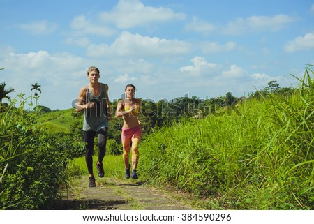 Young couple running in the park, Ubud, Bali - stock photo