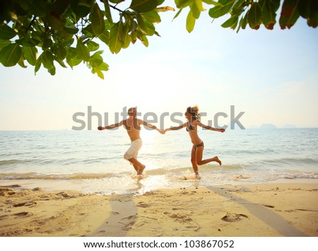 Young couple running on a sandy beach at sunset - stock photo