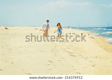 Young couple running on the sandy beach with barefoot in back view, guy wearing gray t shirt, yellow pants, girl dressing in strapless blue sun dress. Bridge, many birds in background. - stock photo