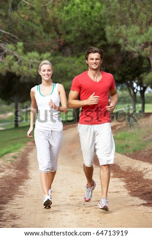 Young couple running through park - stock photo