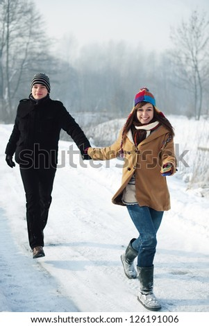 Young couple running through the park - stock photo