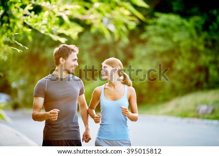 Young couple running together in summer day - stock photo