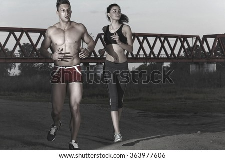 Young couple running together outdoors in beautiful volcanic landscape. Woman trail runner training for marathon run with male model jogging in background. - stock photo
