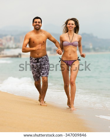 Young couple runs at beach near the sea
