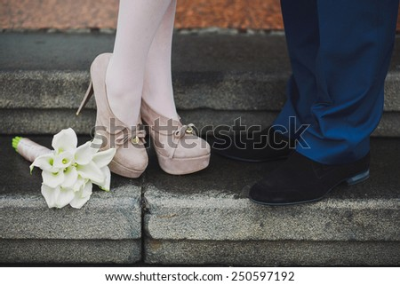 Young couple's legs. Woman and man in love. First date. Dating. Proposal. Lovers kissing. Beautiful white calla lily flowers - stock photo