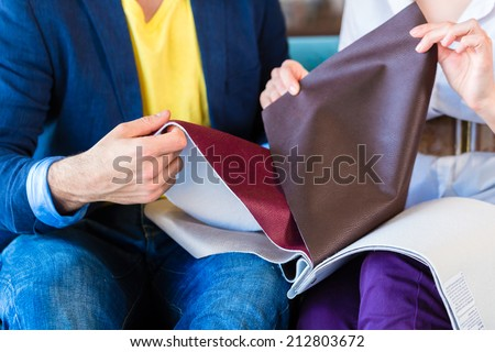Young couple selecting together seat cover for sofa in furniture store - stock photo