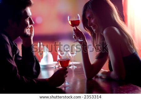 Young couple sharing a glass of red wine in restaurant, celebrating or on romantic date. Focus on woman with glass.
